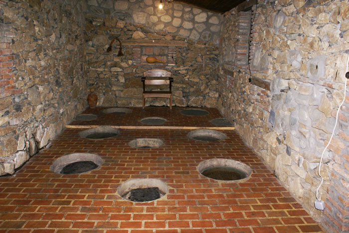 A typical Georgian wine cellar with the holes in the ground for the qvevri's.