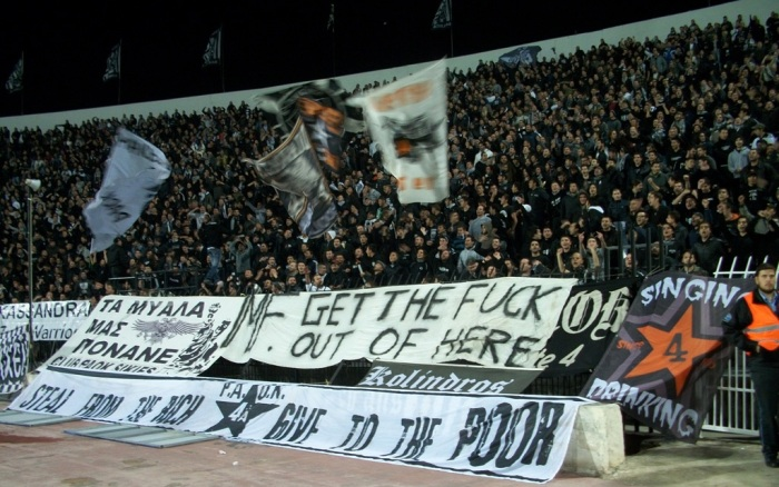 And we stay in Greece. This is PAOK Salonica. Their banner says singing and drinking. PAOK-fans are known to mix cola with a cheap Greek retsina called Malamatina. This cocktail is called Touba Libre, after their stadium Touba.