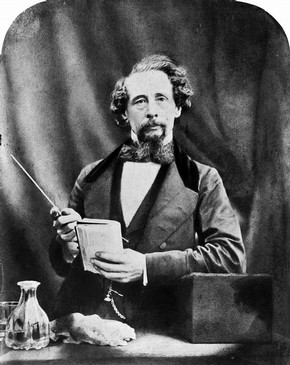Charles Dickens as we like him best, with a sneaky hidden drink next to him.