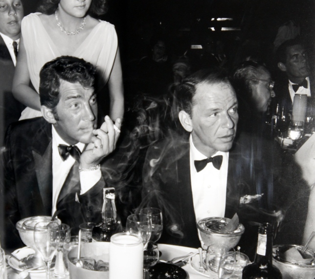 Frank Sinatra (right) and his buddy Dean Martin in a classic pose; smoking and drinking on a night out.