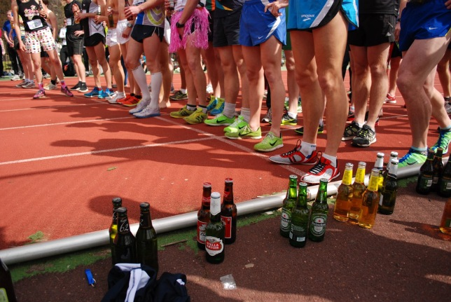 Contestants and beers are lined up before the start of a Beer Mile.