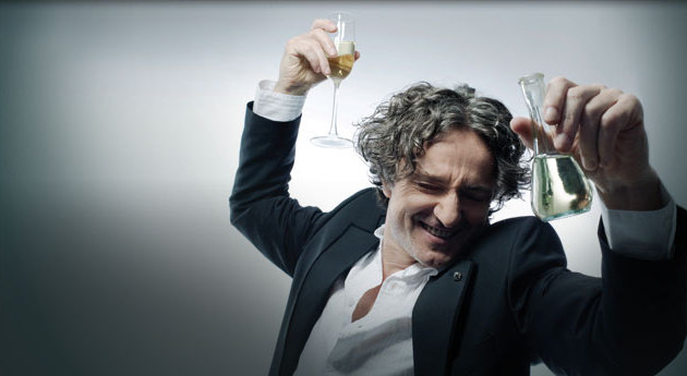 Goran Bregovic poses with glasses filled with champagne and rakija.