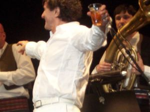 Goran Bregovic in a classic pose in Melbourne, Australia. As he hypes up his orchestra with his right hand, he encourages the audience to drink with his whisky glass in the left.